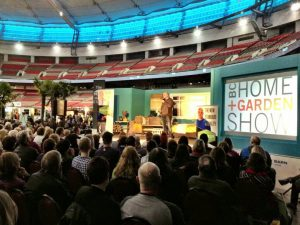 Speaker on stage in front of a crowd at the National Home Show